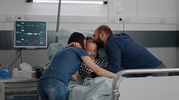Genitori felici che visitano la figlia malata che abbracciano il bambino durante l'esame della malattia