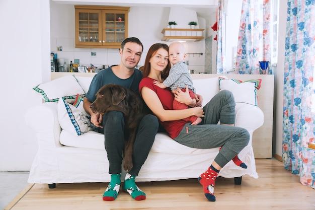 Genitori felici con bambino e cane sul divano a casa interni lifestyle family concept