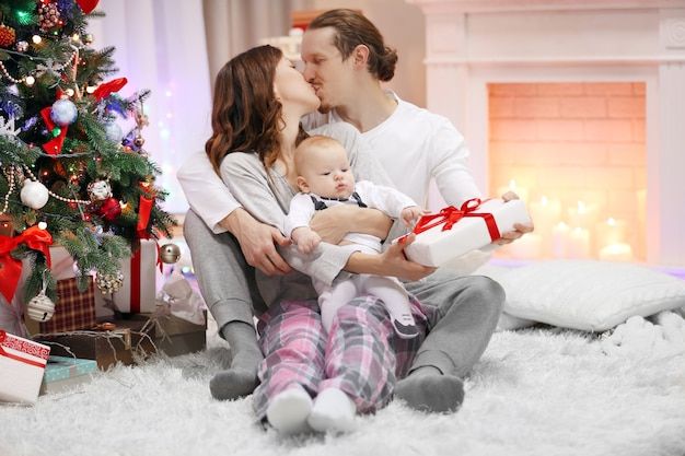 Genitori felici con il bambino vicino all'albero di natale sul pavimento nella stanza decorata