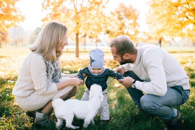 Genitori felici con il bambino che trascorrono tempo alla natura nel giorno soleggiato