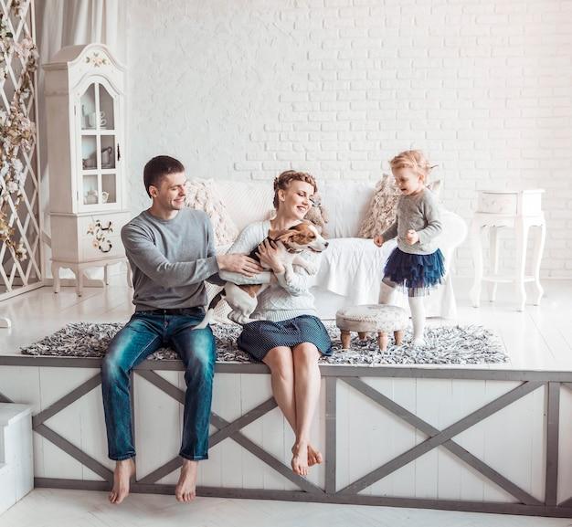 Genitori felici con figlia di cinque anni e il loro cane nell'accogliente soggiorno
