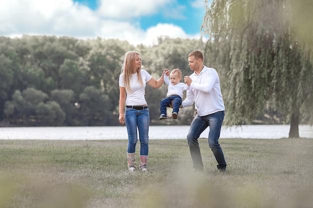 Genitori felici con il loro figlioletto che camminano insieme nel parco di primavera