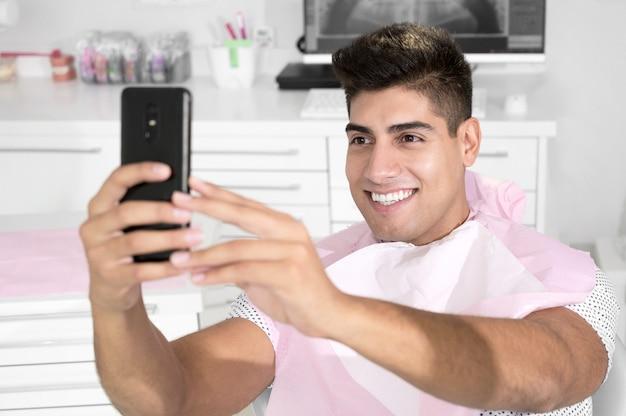 Paziente felice che prende selfie presso la clinica odontoiatrica, il paziente tiene in mano lo smartphone e mostra la sua s...
