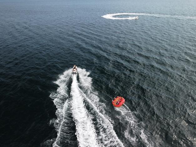 Le persone felici nuoteranno su un materasso ad aria dietro una moto d'acqua i turisti cavalcano il gonfiabile
