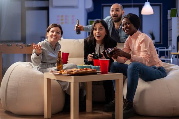 Persone felici che si godono il gioco su console dopo il lavoro in ufficio