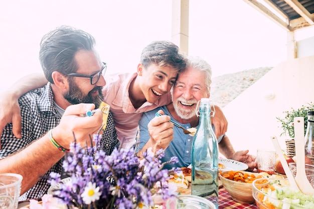 Il concetto di famiglia di persone felici ridono e si divertono insieme a tre diverse generazioni di età: nonno, padre e giovane figlio adolescente, tutti insieme mangiano a pranzo