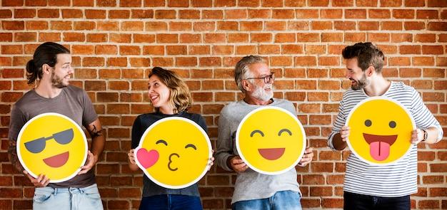Persone felici tenendo emoticon positivo