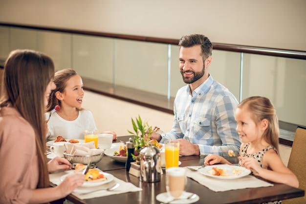 Gente felice. famiglia sorridente che si siede al tavolo e che sembra felice
