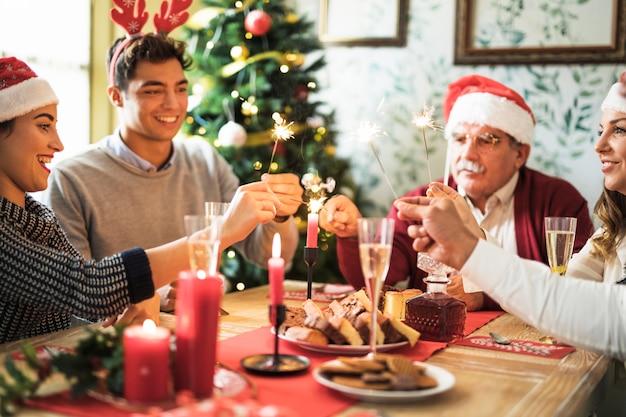 Le persone felici con bengala incendi al tavolo festivo