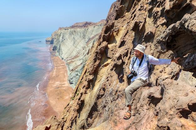 Felice fotografo viaggiatore seduto sul bordo della scogliera, isola di hormuz, hormozgan, iran.