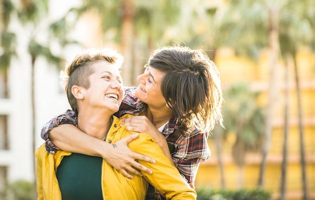 Fidanzate giocose felici innamorate che condividono il tempo insieme durante il viaggio sull'abbraccio sulle spalle