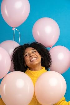 La donna africana felice felice che tiene un sacco di palloncini rosa gode di una festa fresca festeggia il compleanno