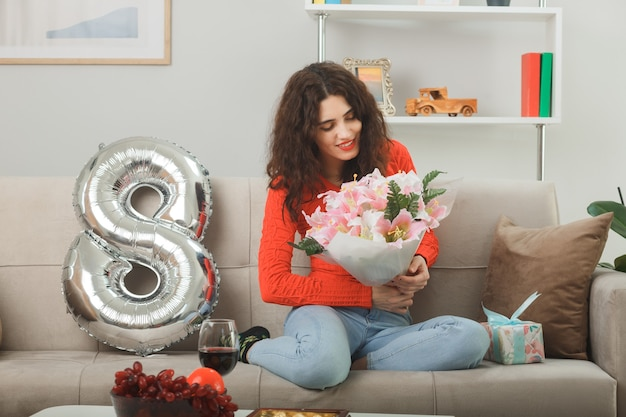 Felice e compiaciuta giovane donna in abiti casual sorridente allegramente seduta su un divano con il palloncino a forma di numero otto che tiene un mazzo di fiori che celebra la giornata internazionale della donna l'8 marzo