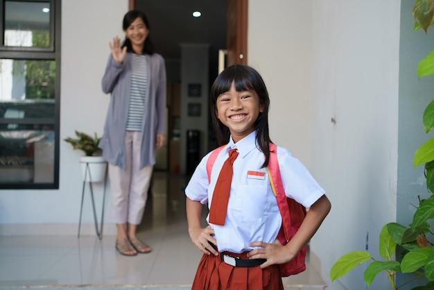 Ritratto felice di bella studentessa primaria asiatica che va a scuola la mattina