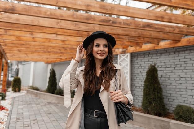 Il ritratto felice di bella giovane ragazza sorridente elegante in vestiti alla moda con un cappotto classico, un cappello alla moda e una borsa di cuoio cammina nella città. moda e stile femminile