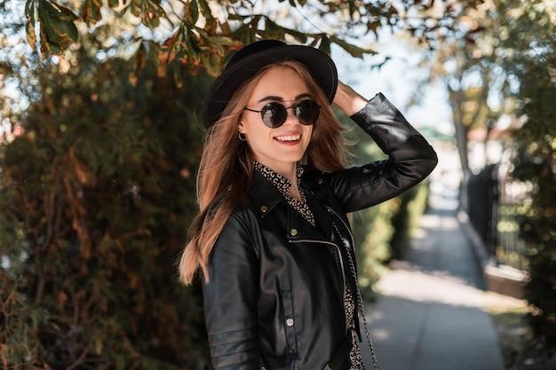 Il ritratto felice di una bellissima modella in abiti alla moda guarda con una giacca di pelle e occhiali da sole alla moda cammina nel parco autunnale