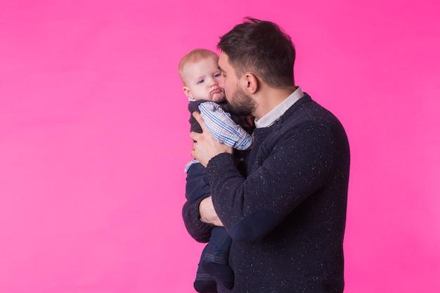 Felice ritratto del padre e del figlio in rosa. in studio.
