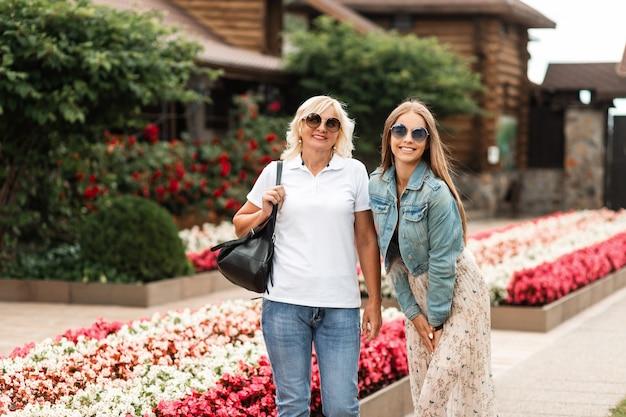 Felice ritratto di due belle donne felice mamma anziana e allegra figlia con occhiali da sole in jeans alla moda vestiti all'aperto durante il fine settimana in famiglia