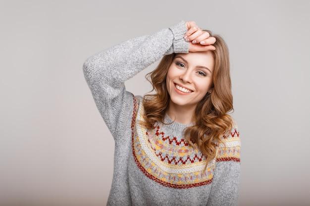 Felice ritratto di una giovane bella donna in un maglione grigio di moda al chiuso