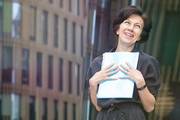 Felice imprenditrice allegra positiva, bella signora sorridente, in possesso di documenti, carte, contratto firmato all'aperto business center.