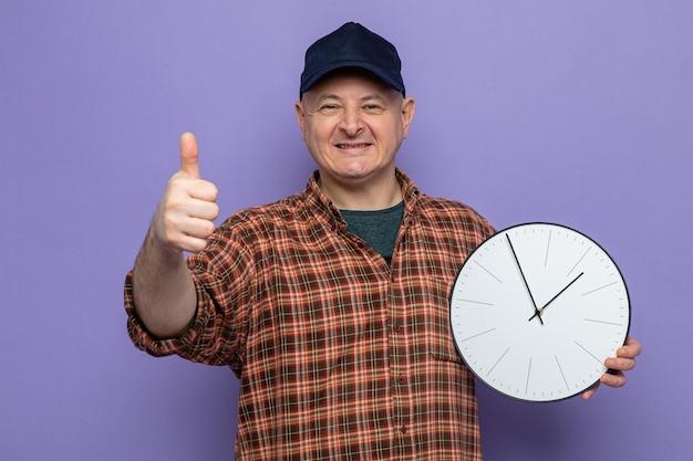 Uomo delle pulizie felice e positivo in camicia a quadri e berretto che tiene l'orologio che sembra sorridente e mostra i pollici in su