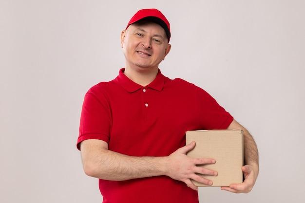 Felice e positivo fattorino in uniforme rossa e cappuccio che tiene una scatola di cartone guardando la telecamera sorridendo fiducioso in piedi su sfondo bianco