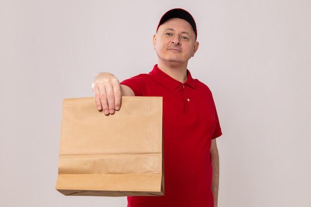Uomo di consegna felice e positivo in uniforme rossa e cappuccio che tiene il pacchetto di carta guardando la fotocamera sorridente fiducioso in piedi su sfondo bianco