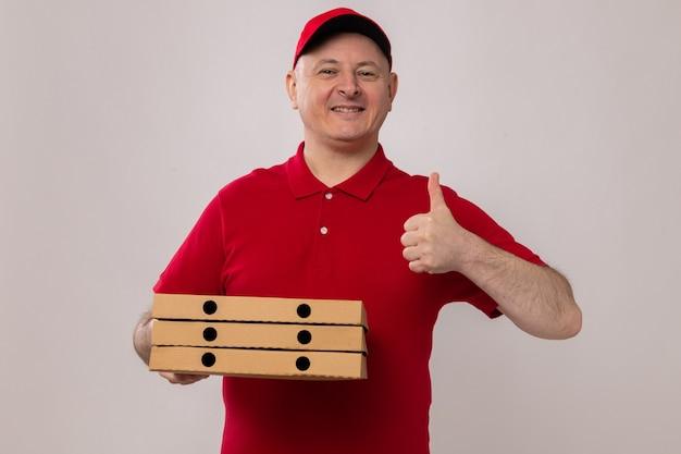 Felice e positivo uomo di consegna in rosso uniforme e cappuccio tenendo scatole per pizza guardando la telecamera sorridendo allegramente mostrando pollice in alto in piedi su sfondo bianco