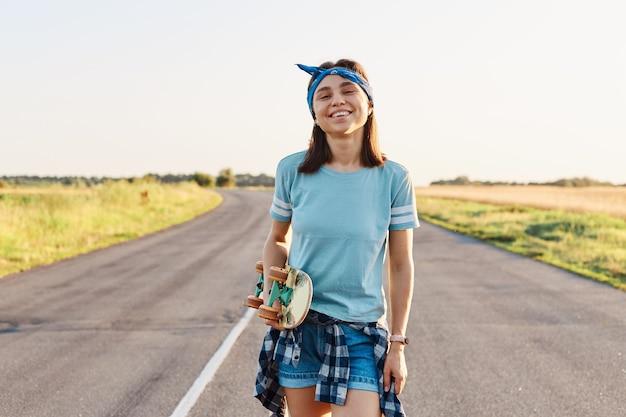 Felice femmina positiva che indossa una maglietta corta e blu e una fascia per capelli, in piedi e guardando la telecamera, tenendo lo skateboard in mano, trascorrendo del tempo all'aperto in estate.