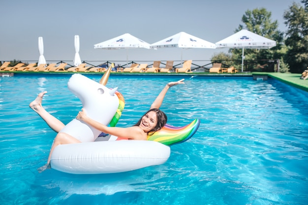 La ragazza felice e positiva sta trovandosi sul materasso di aria nel mezzo della piscina. tiene le mani e le gambe in aria. la ragazza si diverte. lei è lì da sola.