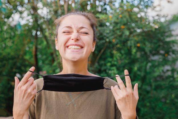 Felice ragazza positiva si toglie la maschera medica protettiva dal viso all'aperto giovane donna che rimuove la ma...