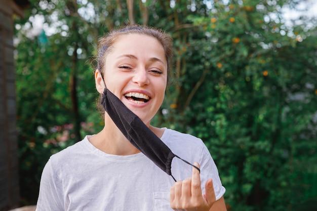 La ragazza positiva felice si toglie la maschera medica protettiva dal viso all'aperto. giovane donna che rimuove la maschera sorridente dopo la vaccinazione. pandemia di coronavirus covid 19 concetto. allergia ai pollini dei fiori primaverili.