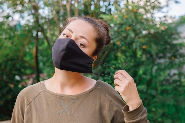 La ragazza positiva felice si toglie la maschera medica protettiva dal viso all'aperto.
