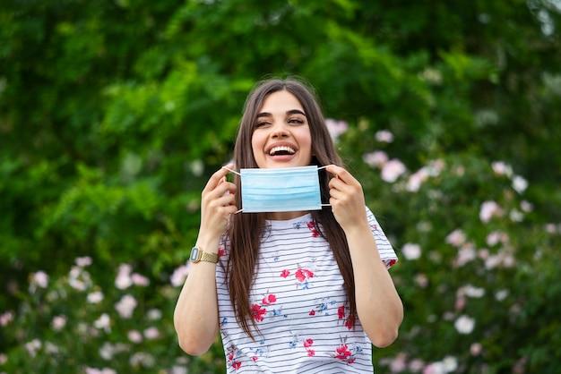 Felice ragazza positiva, giovane e bella donna si toglie la maschera protettiva sterile protettiva dal viso all'aperto, sorridendo.