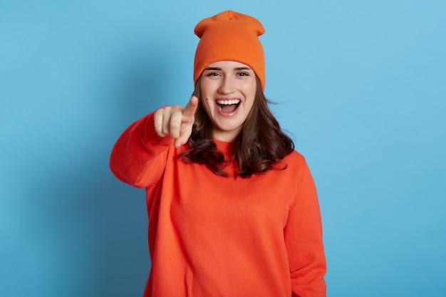 Felice femmina che ride positiva che indossa un maglione e cappello che punta il dito alla telecamera e prende in giro qualcuno, essendo di buon umore, ridicolizzando e satirizzando, isolato sopra il muro blu