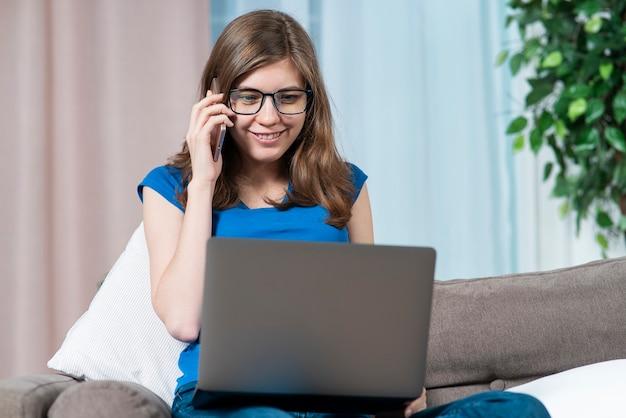 La giovane bella donna della ragazza teenager positiva felice in vetri sta parlando sul suo telefono mobile delle cellule usando