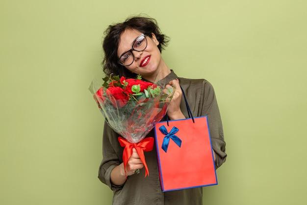 Donna felice e positiva con i capelli corti che tiene il mazzo di fiori e il sacchetto di carta con i regali che sorridono allegramente celebrando la giornata internazionale della donna