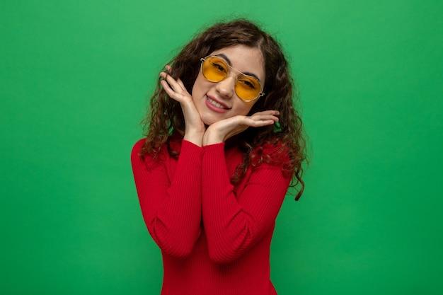 Felice e positiva giovane bella donna in dolcevita rosso che indossa occhiali gialli sorridendo allegramente con le mani sul viso in piedi sul muro verde