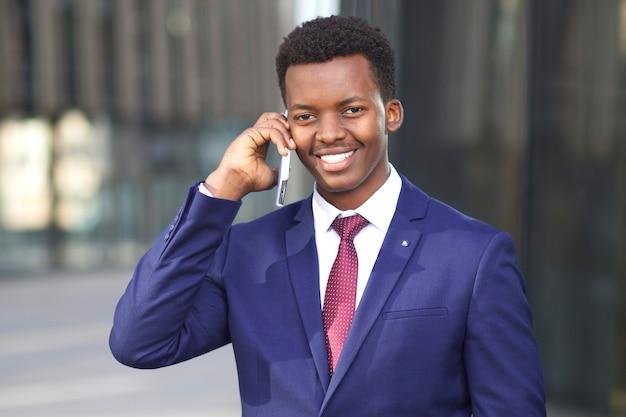 Felice positivo giovane nero africano afroamericano imprenditore parlando al cellulare, sorridendo