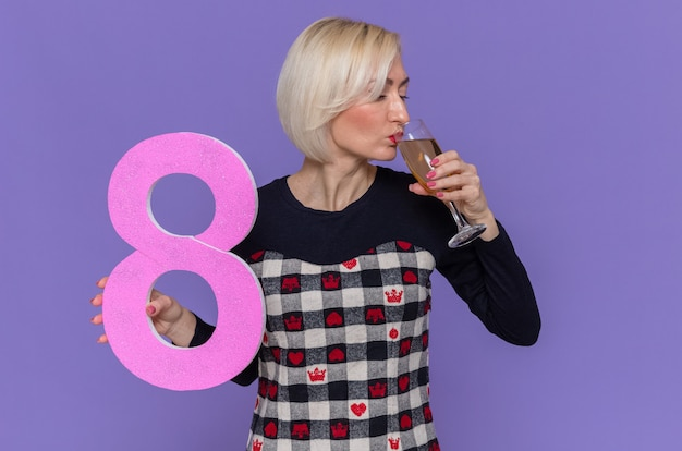 Felice e positiva giovane donna con il numero otto in cartone e bicchiere di champagne bevendo per celebrare la giornata internazionale della donna marzo