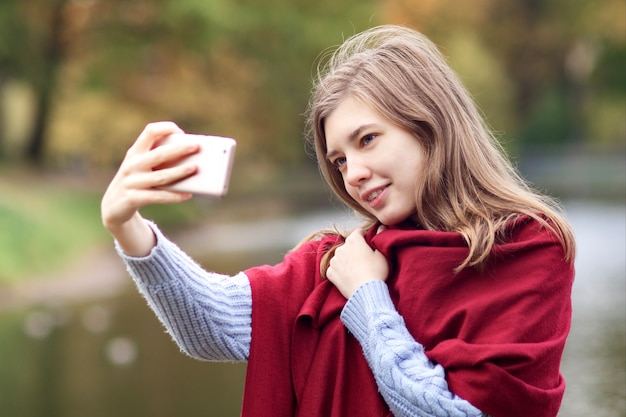 Felice positivo giovane donna prendendo selfie, foto di se stessa con lo smartphone in autunno