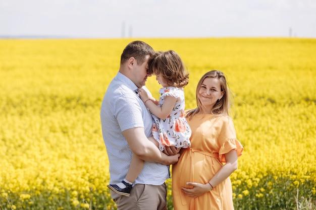 Felice famiglia incinta con la piccola figlia di trascorrere del tempo insieme in un campo di colza giallo il giorno d'estate