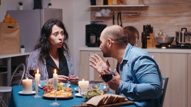 Felice donna incinta delusa dal marito durante una cena romantica che mostra un test positivo. uomo infelice, nervoso, arrabbiato che combatte con la moglie, bambino indesiderato, frustrato per i risultati.