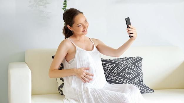 Felice donna incinta in abito bianco ha una videochiamata con il futuro padre tramite smartphone seduta sul divano con morbidi cuscini firmati a casa
