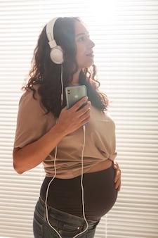 Felice donna incinta con i capelli ricci che ascolta musica in cuffia