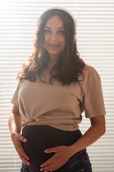Felice donna incinta con capelli ricci che ascolta musica in cuffia