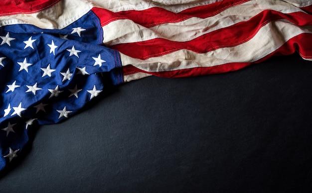 Concetto felice di giorno dei presidenti con la bandiera degli stati uniti su fondo di legno nero.