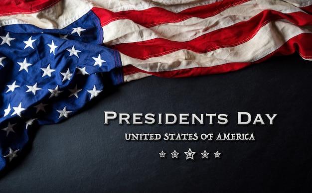 Concetto felice di giorno dei presidenti con la bandiera degli stati uniti su legno nero