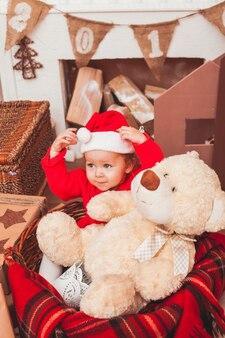 Felice bel bambino vestito in costume da babbo natale con regali di natale