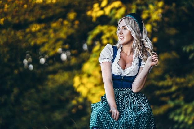 Ragazza bionda graziosa felice in dirndl, vestito tradizionale da festival della birra, sedentesi all'aperto con gli alberi colourful blured dietro